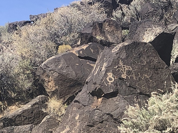 In this March 21, 2020, photo, petroglyphs at the Petroglyph National Monument, one of the largest petroglyph sites in North America, are shown in Albuquerque, N.M. Petroglyph National Monument Superintendent Nancy Hendricks said Saturday, May 9, 2020 crews have reported three episodes of vandalism this year at the monument. (AP Photo/Russell Contreras)