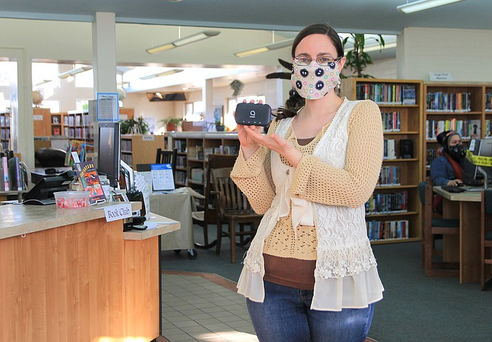 Librarian Mary Corcoran displays one of the 10 new Wi-Fi hotspots available at the Williams Public Library. Patrons can check out the hotspots similar to checking out a book. Wi-Fi can be accessed outside of the library as well. (Wendy Howell/WGCN)