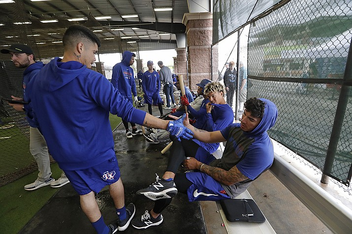 In this March 12, 2020, file photo, Texas Rangers minor-league players Chris Seise, right, and Kevin Mendoza greet each other in the batting cages in Surprise, Ariz. Spring training could be delayed for Double-A and Class A players if major leaguers are not vaccinated for the novel coronavirus by the time big league practice is scheduled to start in mid-February. Major League Baseball, which has taken over operation of the minors, gave notice to minor league teams and big league clubs Monday, Jan. 4. (Elaine Thompson, AP File)