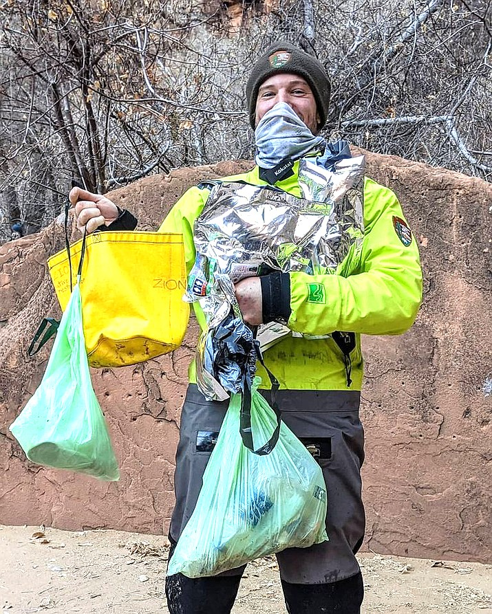 A ranger, in a protective drysuit, holds bags of trash collected in the Narrows in Zion National Park. (Photo/NPS)