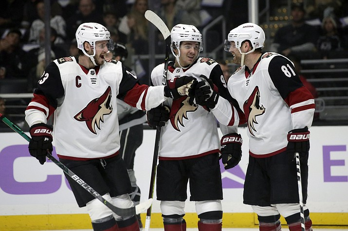 In this Saturday, Nov. 23, 2019, file photo, Arizona Coyotes center Phil Kessel, right, celebrates his goal with defenseman Oliver Ekman-Larsson, left, of Sweden, and center Clayton Keller, center, during the first period of an NHL hockey game against the Los Angeles Kings in Los Angeles. Bolstered by a taste of playoff success, the Coyotes are aiming to go even deeper in a unique 2021 season with roster additions who are expected to add a level of toughness and tenacity. (AP Photo/Alex Gallardo, File)