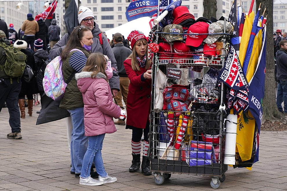 People attending a rally at Freedom Plaza Tuesday, Jan. 5, 2021, in Washington, in support of President Donald Trump, look at merchandise offered for sale by a vendor. (AP Photo/Jacquelyn Martin)