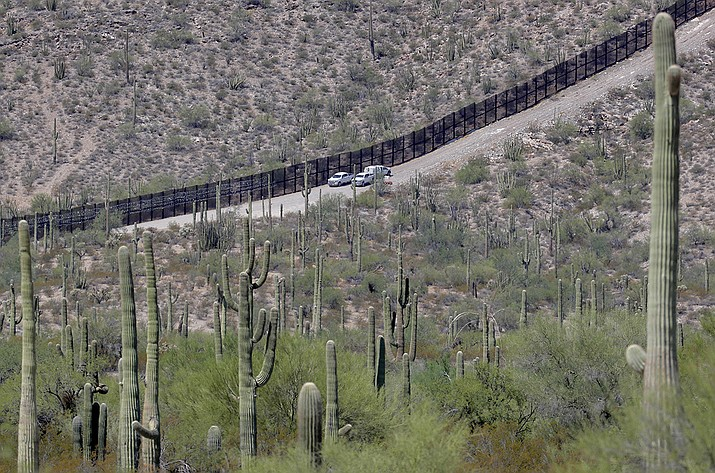 In this Aug. 22, 2019, file photo, U.S. Customs and Patrol agents sit along a section of the international border wall that runs through Organ Pipe National Monument in Lukeville, Ariz. A public-private project that maps the bodies of border crossers recovered from Arizona's inhospitable deserts, valleys and mountains said this week of Monday, Jan. 4, 2021 that it documented 227 such deaths in 2020, the highest in a decade following the hottest, driest summer in state history. (Matt York, AP File)