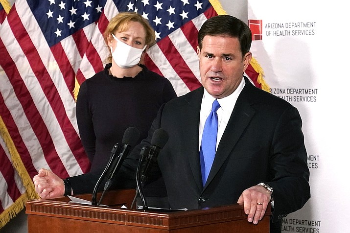 Arizona Gov. Doug Ducey answers a question about the arrival of a COVID-19 vaccine in Arizona, while Arizona Department of Health Services Director Dr. Cara Christ listens in Phoenix. (AP Photo/Ross D. Franklin, Pool, File)