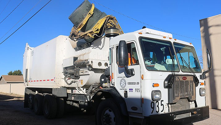 A Kingman garbage truck picks up a load of trash in an alley. A customer survey reveals that most city solid waste customers are satisfied with the current level of service. (Miner file photo)