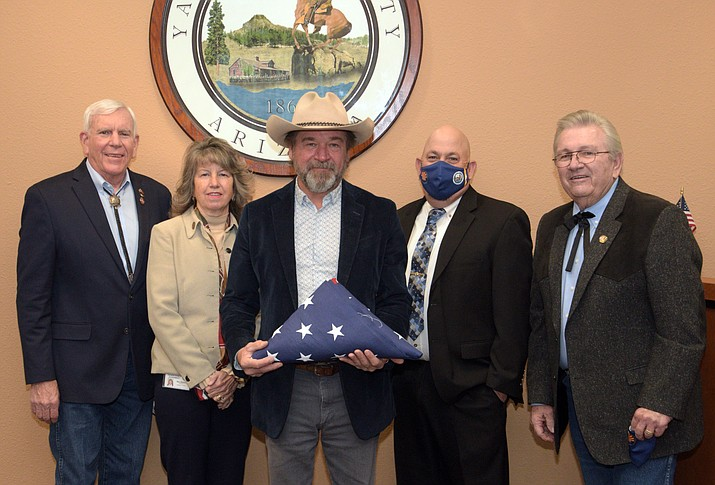 Recently retired Sheriff Scott Mascher (center) holds a U.S. Flag given to him by the Yavapai County Board of Supervisors during the board's Jan. 6 meeting. Pictured left to right are: District 1 Supervisor Harry Oberg, District 5 Supervisor and Vice-Chair Mary Mallory, Mascher, District 2 Supervisor James Gregory and Chairman Craig Brown. (Yavapai County/Courtesy)