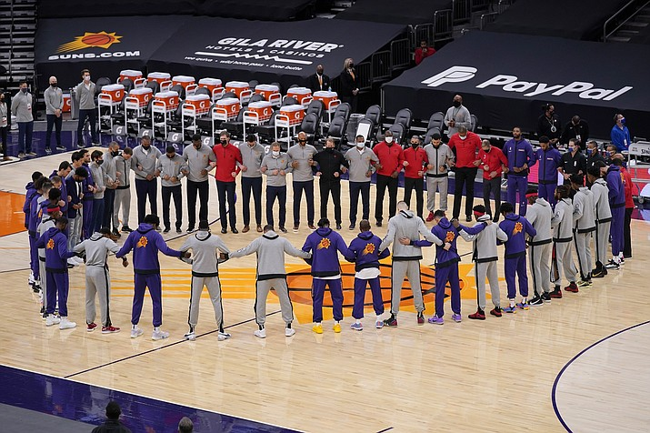 Members of the Phoenix Suns and the Toronto Raptors form a circle during the American national anthem prior to a basketball game Wednesday, Jan. 6, 2021, in Phoenix. (Ross D. Franklin/AP)