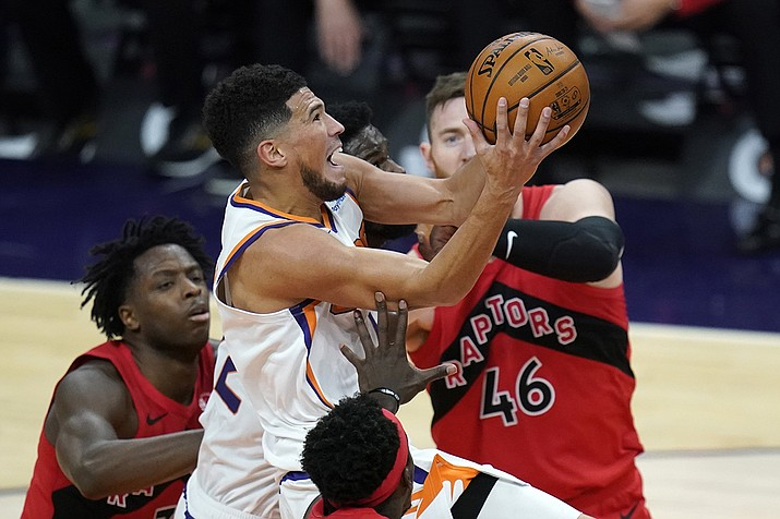 Phoenix Suns guard Devin Booker, middle, drives past Toronto Raptors center Aron Baynes (46) and Raptors forward OG Anunoby, left, during the second half of an NBA basketball game Wednesday, Jan. 6, 2021, in Phoenix. (Ross D. Franklin/AP)