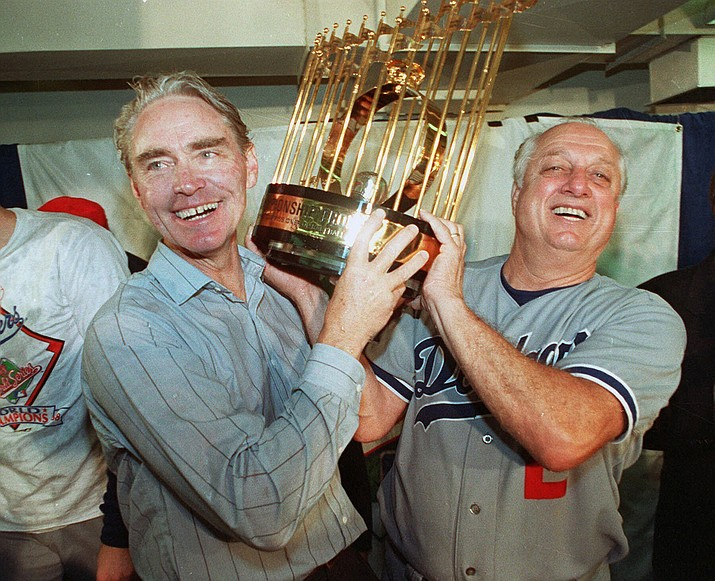 Los Angeles Dodgers manager Tommy Lasorda, right, and Fred Claire, Dodger Vice President, hoist the World Series trophy following their team's 5-2 win over the Oakland Athletics in Oakland, Calif., in this Oct. 20, 1988, file photo. Lasorda, the fiery Hall of Fame manager who guided the Los Angeles Dodgers to two World Series titles and later became an ambassador for the sport he loved during his 71 years with the franchise, has died. He was 93. The Dodgers said Friday, Jan. 8, 2021, that he had a heart attack at his home in Fullerton, California. (AP Photo/File)
