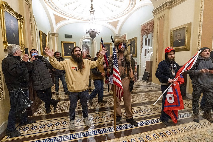 In this Wednesday, Jan. 6, 2021 file photo supporters of President Donald Trump are confronted by U.S. Capitol Police officers outside the Senate Chamber inside the Capitol in Washington. Jacob Anthony Chansley, the Arizona man with the painted face and wearing a horned, fur hat, was taken into custody Saturday, Jan. 9, 2021 and charged with counts that include violent entry and disorderly conduct on Capitol grounds. (AP Photo/Manuel Balce Ceneta, file)