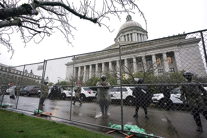 Members of the Washington National Guard stand near a fence surrounding the Capitol in anticipation of protests Monday, Jan. 11, 2021, in Olympia, Wash. State capitols across the country are under heightened security after the siege of the U.S. Capitol last week. (Ted S. Warren/AP)
