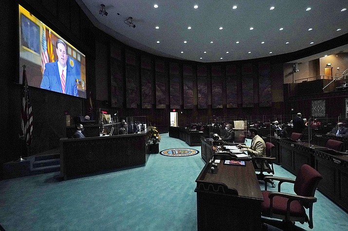 In a darkened and nearly empty Arizona House of Representatives, Republican Gov. Doug Ducey delivers a remote State of the State address during the opening of the Arizona Legislature at the state Capitol Monday, Jan. 11, 2021, in Phoenix. (Ross D. Franklin/AP)