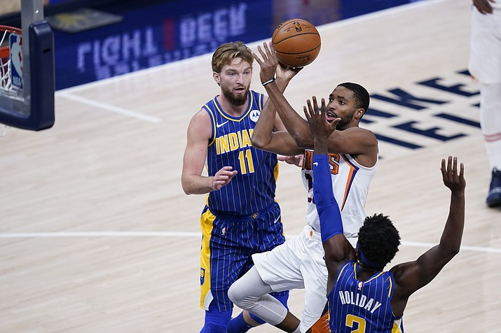 Phoenix Suns' Mikal Bridges (25) shoots against Indiana Pacers' Aaron Holiday (3) during the first half of an NBA basketball game, Saturday, Jan. 9, 2021, in Indianapolis. (AP Photo/Darron Cummings)
