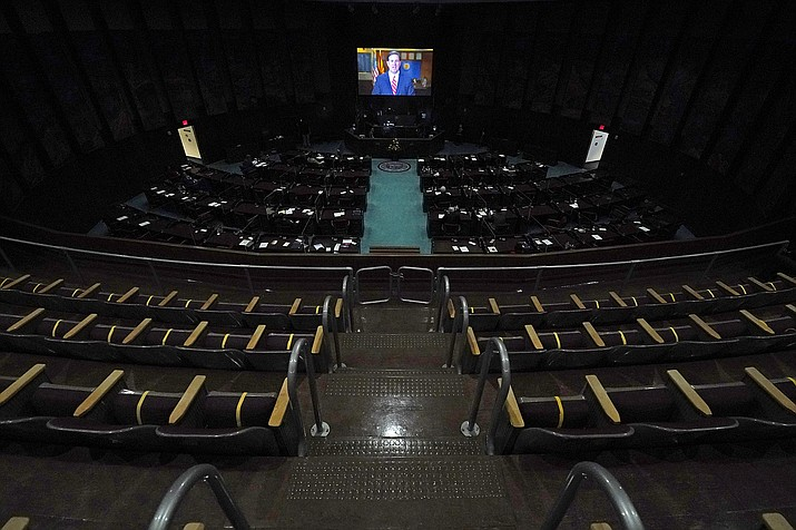 In a darkened and nearly empty Arizona House of Representatives floor, Republican Gov. Doug Ducey delivers a remote state of the state address during the opening of the Arizona Legislature at the state Capitol Monday, Jan. 11, 2021, in Phoenix. (AP Photo/Ross D. Franklin, Pool)