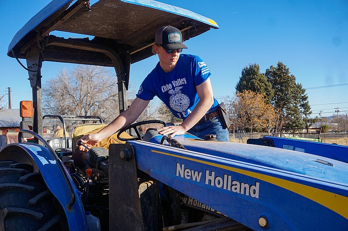 Chino Valley FFA student intern Gavin MacAulay turns on a tractor before starting a day's work on Tuesday, Jan. 5, 2021, at the Cooper Agricultural Center in Chino Valley. Since MacAulay is an intern, he's been the only student working in person for the Chino Valley FFA as Chino Valley Unified School District operates under a distance-learning model due to the rise in COVID-19 cases in the county. (Aaron Valdez/Review)