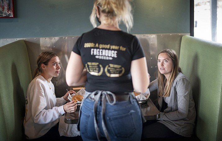 In this Jan. 11, 2021, file photo, Grace Mathre, server at Longfellow Grill, checks on University of St. Thomas students Lundsey Schulz and Maren Daggett in Minneapolis. As the U.S. finds itself in the most lethal phase of the coronavirus outbreak yet, governors and local officials in hard-hit parts of the country are showing little willingness to impose any new restrictions on businesses to stop the spread. (Glen Stubbe/Star Tribune via AP, File)