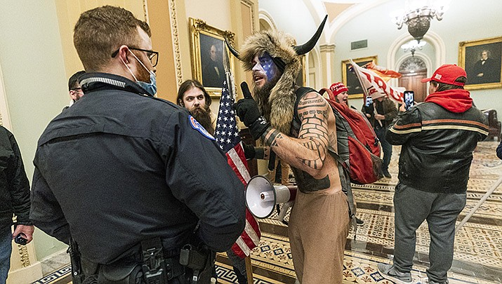 Jacob Anthony Chansley of Arizona, wearing a fur hat with horns, is confronted by U.S. Capitol Police officers outside the Senate Chamber inside the Capitol in Washington on Wednesday, Jan. 6. He was charged and taken into custody Saturday. (AP Photo/Manuel Balce Ceneta, File)