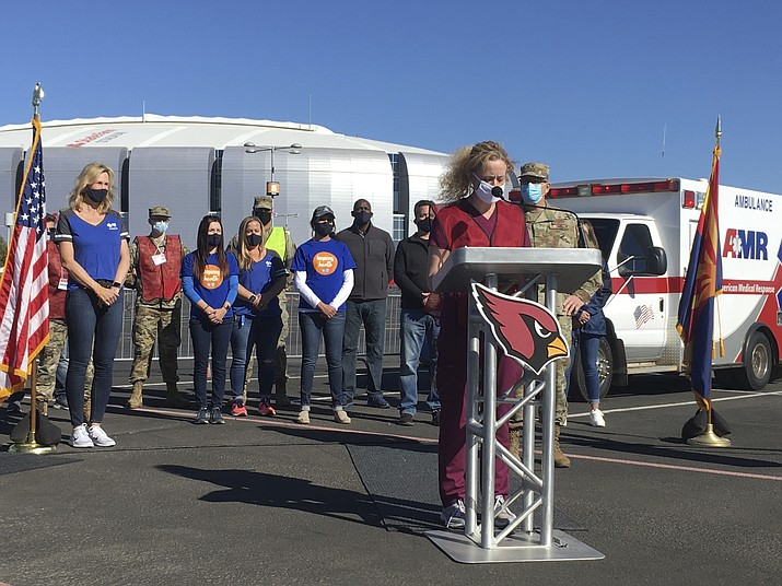Dr. Cara Christ, director of the Arizona Department of Health Services, speaks to reporters in the parking lot of the State Farm Stadium in Glendale, Ariz., on Monday, Jan. 11, 2021. The Arizona Cardinals' stadium opened as a vaccination site Monday that will be a 24-7 operation. (Terry Tang/AP)