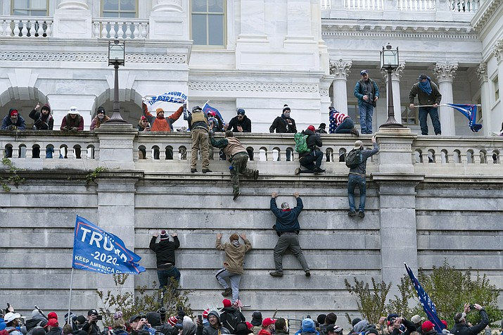 Supporters of President Donald Trump climb the west wall of the U.S. Capitol on Wednesday, Jan. 6, 2021, in Washington, D.C. (Jose Luis Magana/AP, file)