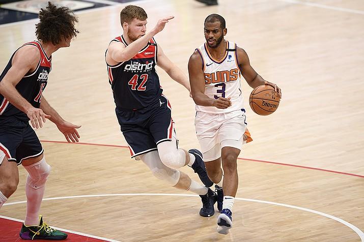 Phoenix Suns guard Chris Paul (3) dribbles next to Washington Wizards forward Davis Bertans (42) and center Robin Lopez (15) during the first half of an NBA basketball game, Monday, Jan. 11, 2021, in Washington. (Nick Wass/AP)