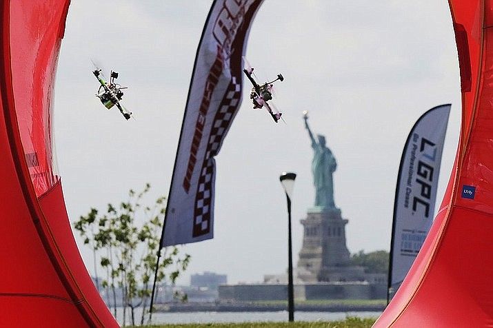 Pilots fly their small racing drones through an obstacle course for the National Drone Racing Championship on Governors Island, a former military installation in New York Harbor, Friday, Aug. 5, 2016. A major sports book is now taking bets on aerial drone races. (AP Photo/Richard Drew, File)