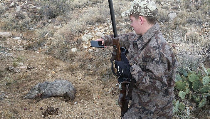A young hunter photographs the javelina he just harvested. (Photo by Don Martin/For the Miner)