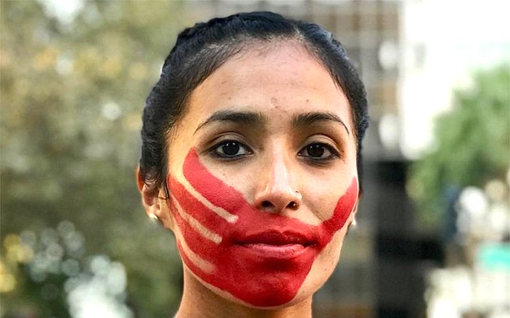 "The red handprint that Jordan Daniel wears across her face represents a message that Missing and Murdered Indigenous Women Movement wants out: ""We will not be silenced."" (Photo courtesy of Devin Whetstone)"