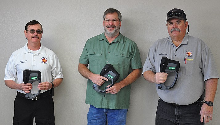 From left, Golden Valley Fire District Chief David Cunningham, Griffith Energy Plant Manager Scott Henry and GVFD Assistant Fire Chief David Martin display MSA Evolution 6000+ thermal imaging cameras that were donated to GVFD by Griffith Energy. (Photo by Butch Meriwether/For the Miner)