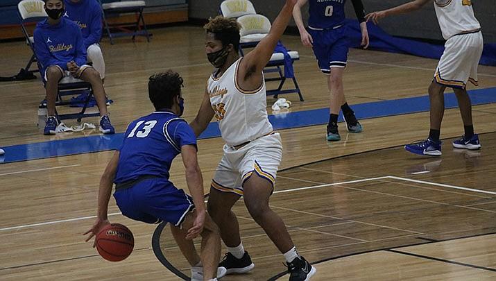 Trevin Zach of Kingman Academy dribbles behind his back as Malachi Brown of Kingman High School defends during Academy's 56-40 boys basketball win on Thursday, Jan. 21. (Photo by Travis Rains/Kingman Miner)