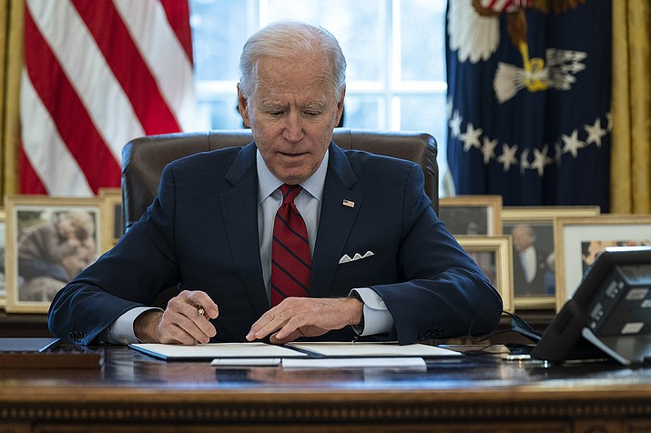 President Joe Biden signs a series of executive orders on health care, in the Oval Office of the White House, Thursday, Jan. 28, 2021, in Washington. (Evan Vucci/AP)