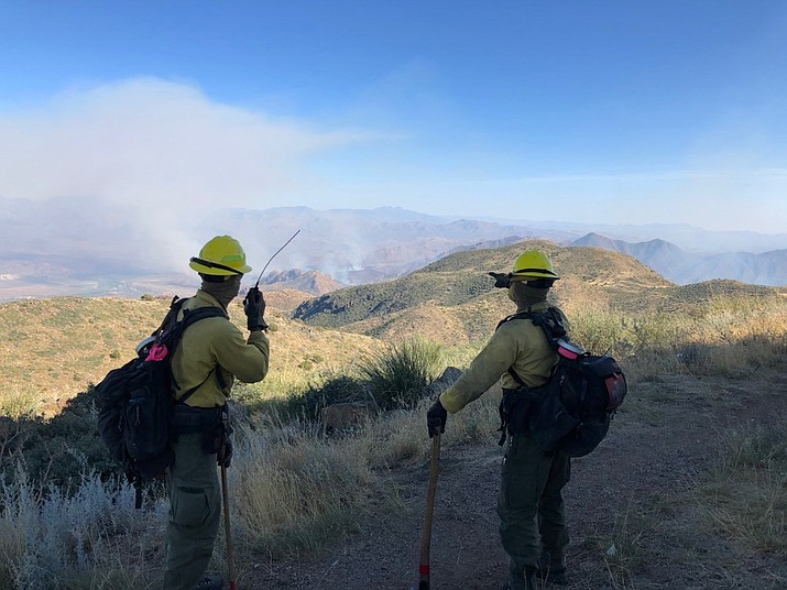 """Firefighters take a look at the """"Sears Fire"""" on Sept. 28, 2020, a wildfire north of Phoenix that destroyed several structures, including multiple homes. The blaze was in the Tonto National Forest during one of the worst fire seasons in nearly a decade in Arizona. (Tonto National Forest Facebook/Courtesy, file)"""