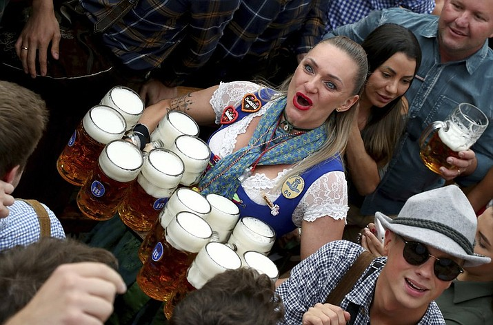 In this Saturday, Sept. 21, 2019 file photo, a waitress holds twelve glasses of beer during the opening of the 186th 'Oktoberfest' beer festival in Munich, Germany. Official data show that beer sales in Germany were down 5.5 percent last year, dragged lower by lengthy closures of bars and restaurants in the coronavirus pandemic. (AP Photo/Matthias Schrader, file)