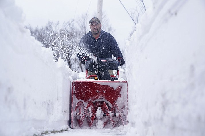 Robert Post, who owns a landscaping company, puts the final touches on a sidewalk he just cleared in Mt. Arlington, N.J., Wednesday, Feb. 3, 2021. This week's winter storm appears to have broken a 122-year-old record for the most snow in a New Jersey community from one storm. The National Weather Service made a preliminary report Tuesday that Mount Arlington in the northern part of the state got 35.5 inches of snow in the three-day storm. (AP Photo/Seth Wenig)