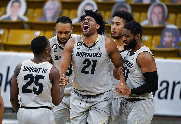 Colorado forward Evan Battey (21) is helped up by, from left, guard McKinley Wright IV, forward Dallas Walton, guard D'Shawn Schwartz and forward Jeriah Horne during the second half of the team's NCAA college basketball game against Arizona on Saturday, Feb. 6, 2021, in Boulder, Colo. Colorado won 82-79. (AP Photo/David Zalubowski)