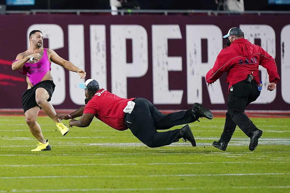 Security tries to grab a fan on the field during the second half of the NFL Super Bowl 55 football game between the Tampa Bay Buccaneers and the Kansas City Chiefs, Sunday, Feb. 7, 2021, in Tampa, Fla. (AP Photo/Mark Humphrey)