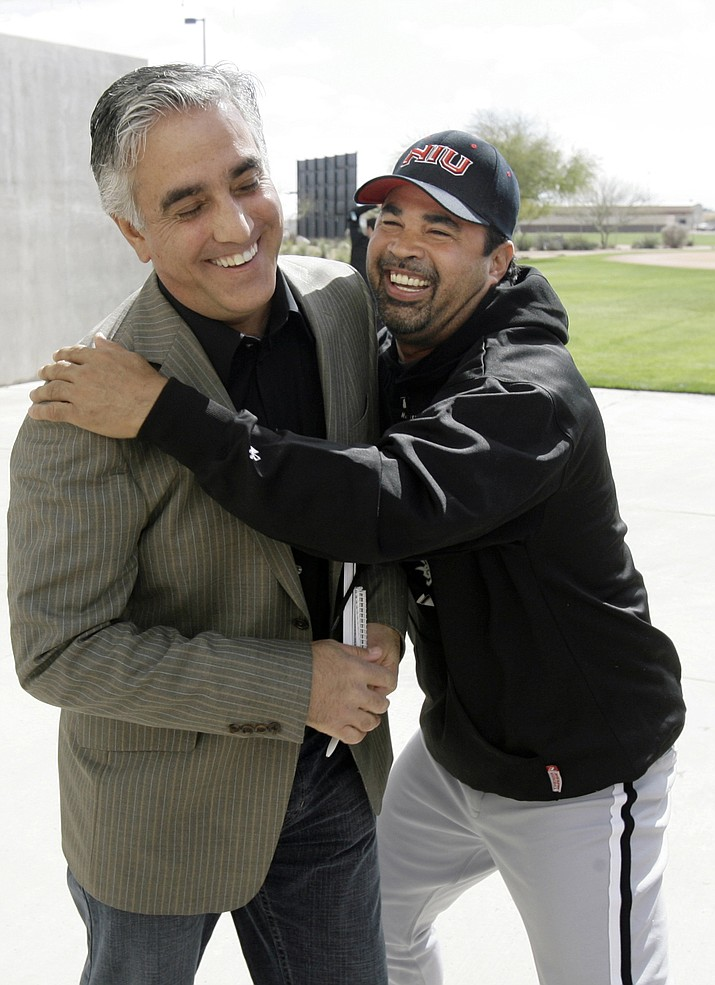 In this Saturday, Feb. 16, 2008, file photo, Chicago White Sox manager Ozzie Guillen, right, jokes with ESPN's Pedro Gomez after a news conference during the first day of baseball spring training for pitchers and catchers, in Tucson, Ariz. Gomez, a longtime baseball correspondent for ESPN who covered more than 25 World Series, died Sunday, Feb. 7, 2021. He was 58. (M. Spencer Green, AP File)