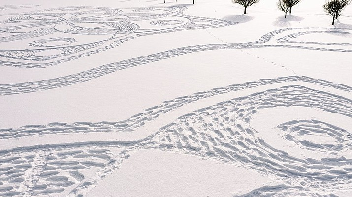 Part of a giant complex geometric pattern formed from thousands of footsteps in the snow in Espoo, Finland, Monday Feb. 8, 2021. The art work design measuring about 160 meters in diameter was made by volunteers in snowshoes under the guidance of local resident and amateur artist Janne Pyykko, but the ephemeral work will only last until the next snowfall or heavy winds. (Pekka Lintusaari via AP)