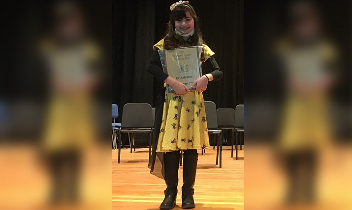 Homeschool fifth-grader Aliyah Alpert holds up her championship plaque after emerging first place in the 75th annual Yavapai County Spelling Bee on Saturday, Feb. 13. She  competed with 13 other contestants from around the county at the Prescott Mile High Middle School auditorium. (Branda Alpert/Courtesy)