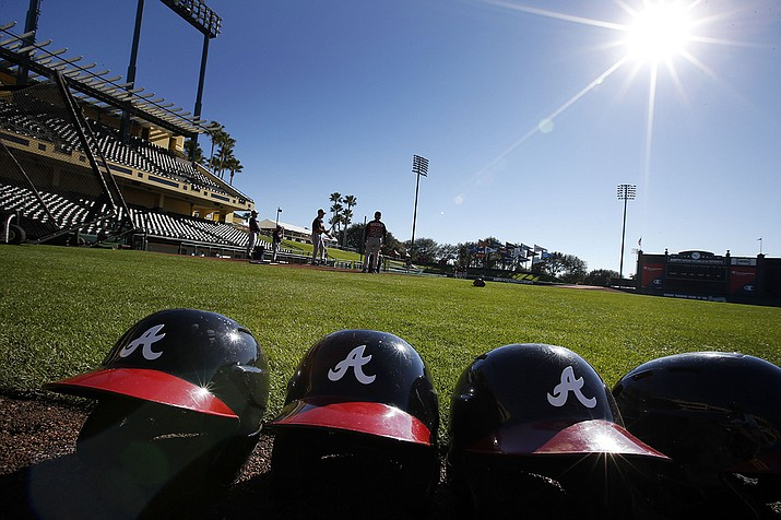 In this Feb. 18, 2014, file photo, Atlanta Braves batting helmets sits on the field under a shining sun during a spring training baseball workout in Kissimmee, Fla. Major League Baseball revamped its spring training exhibition schedule because of the pandemic, cutting travel for Florida-based teams in an effort to avoid the novel coronavirus, the league announced Friday, Feb. 12, 2021. (Alex Brandon, AP File)
