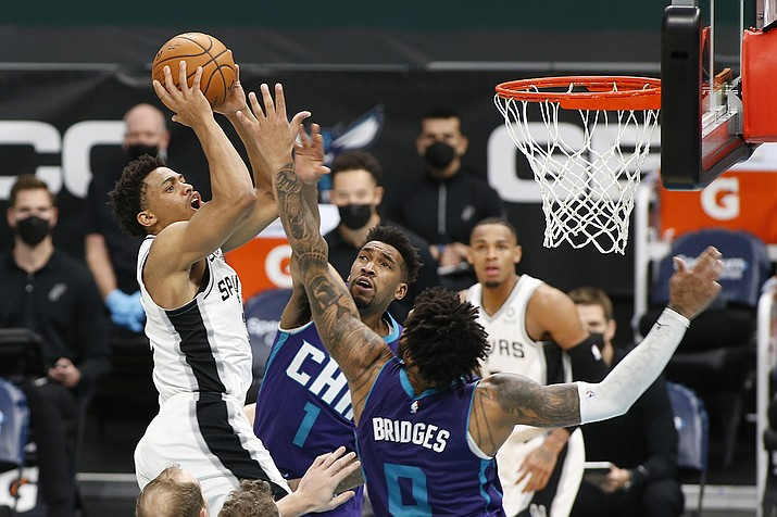 San Antonio Spurs forward Keldon Johnson, left, shoots over Charlotte Hornets guard Malik Monk (1) and forward Miles Bridges during the second half of an NBA basketball game in Charlotte, N.C., Sunday, Feb. 14, 2021. (Nell Redmond/AP)