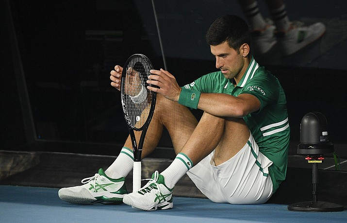 Serbia's Novak Djokovic sits down at the back of the court between games during his quarterfinal against Germany's Alexander Zverev at the Australian Open tennis championship in Melbourne, Australia, Tuesday, Feb. 16, 2021. (Andy Brownbill/AP)
