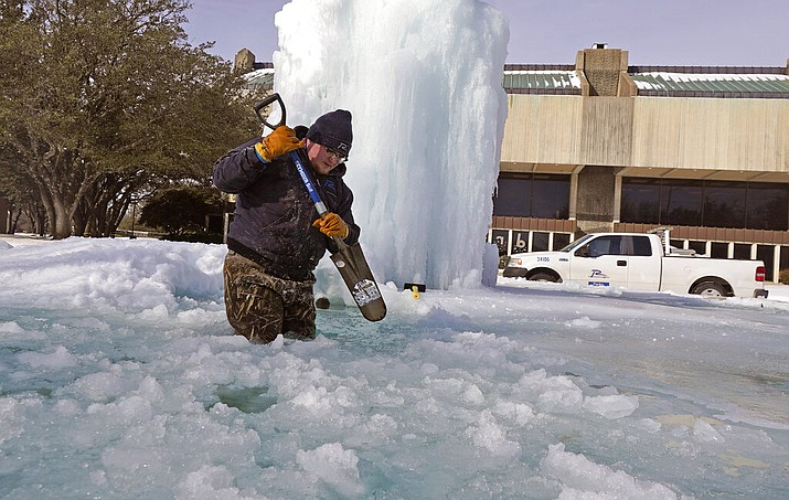 City of Richardson worker Kaleb Love breaks ice on a frozen fountain Tuesday, Feb. 16, 2021, in Richardson, Texas. Temperatures dropped into the single digits as snow shut down air travel and grocery stores. (AP Photo/LM Otero)