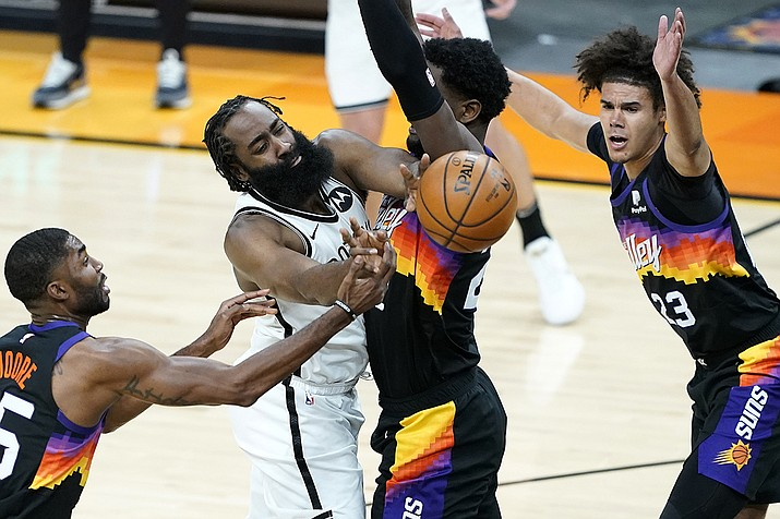 Brooklyn Nets guard James Harden dishes around Phoenix Suns center Deandre Ayton, right, during the first half of an NBA basketball game, Tuesday, Feb. 16, 2021, in Phoenix.(Matt York/AP)