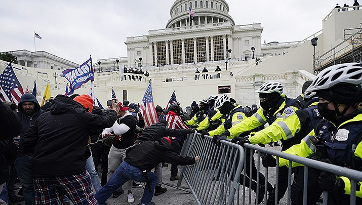An Arizona woman charged in connection with the Jan. 6 onslaught of the U.S. Capitol bragged in a Snapchat video that she was recently recruited by a Kansas City chapter of the Proud Boys. Protesters are shown battling police outside the Capitol on Jan. 6. (AP file photo)