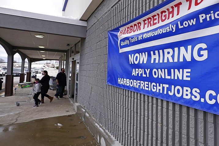 """In this Dec. 10, 2020 file photo, a """"Now Hiring"""" sign hangs on the front wall of a Harbor Freight Tools store in Manchester, N.H. U.S. employers cut back sharply on hiring in December, particularly in pandemic-hit industries such as restaurants and hotels, as soaring virus infections and government restrictions weakened the economy that month. The number of available jobs rose slightly and layoffs fell, according to the Labor Department's Tuesday report, known as the Job Openings and Labor Turnover Survey, or JOLTS. (AP Photo/Charles Krupa, File)"""