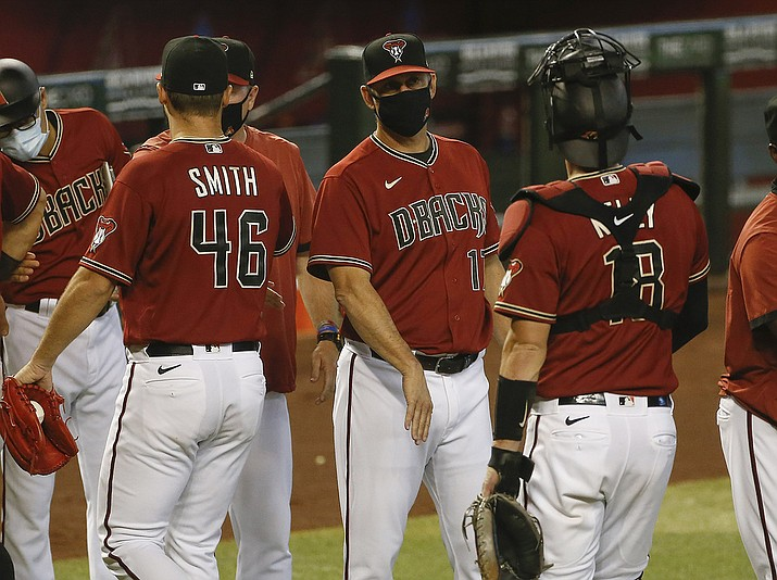 Arizona Diamondbacks baseball team manager Torey Lovullo, center, greets his players after their win over the Colorado Rockies in Phoenix, in this Sunday, Sept. 27, 2020, file photo. The 55-year-old Lovullo enters his fifth year with the Diamondbacks — and the final year of his current contract — under a substantial amount of scrutiny. Lovullo shrugged off any notion that he's feeling added pressure on Wednesday, Feb. 17, 2021, when the team's pitchers and catchers went through their first workouts in Scottsdale, Arizona. (Darryl Webb, AP File)