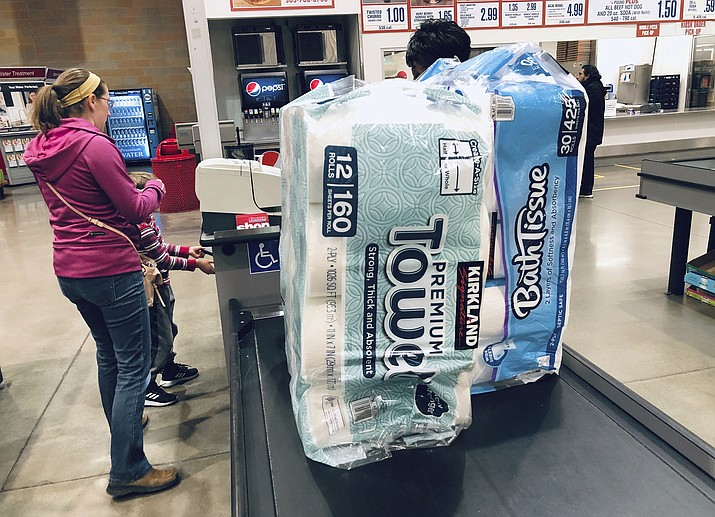 In this March 23, 2020 file photo, a shopper pays for packages of toilet paper and hand towels at a Costco warehouse in Lone Tree, Colo. As Americans stayed home and ordered online during the lockdowns of 2020, our homes became filled with all sorts of purchases: toilet paper, crafts and plenty of board games. But as time wears on, what do you do if you find yourself with too much stuff? There are some easy ways to sell or donate the things you have in your house. (David Zalubowski, AP File)