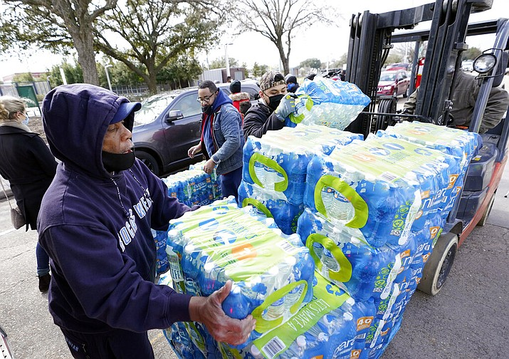 Donated water is distributed to residents, Thursday, Feb. 18, 2021, in Houston. Houston and several surrounding cities are under a boil water notice as many residents are still without running water in their homes. (AP Photo/David J. Phillip)