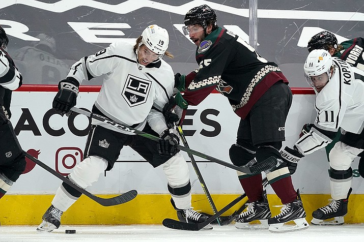 Los Angeles Kings right wing Alex Iafallo (19) battles with Arizona Coyotes defenseman Jason Demers, second from right, for the puck as Kings center Anze Kopitar (11) looks on during the first period of an NHL hockey game Thursday, Feb. 18, 2021, in Glendale, Ariz. (Ross D. Franklin/AP)