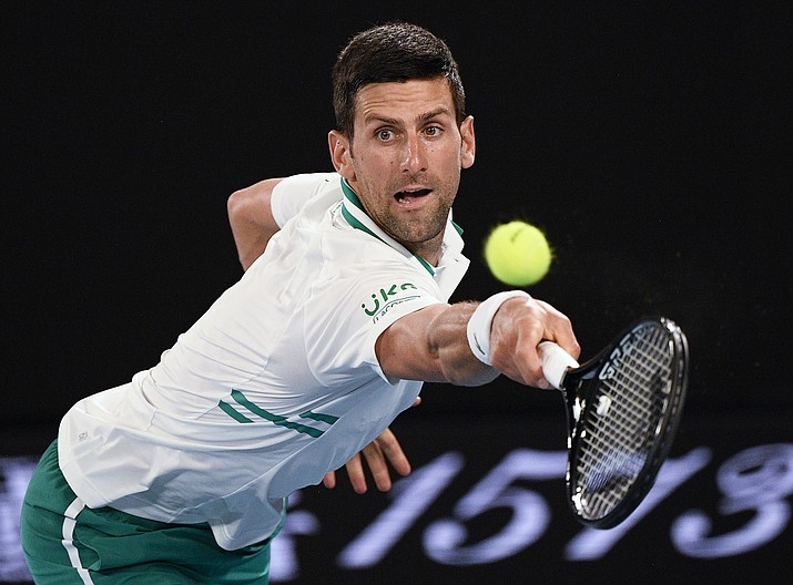 Serbia's Novak Djokovic hits a backhand return to Russia's Aslan Karatsev during their semifinal match at the Australian Open tennis championship in Melbourne, Australia, Thursday, Feb. 18, 2021.(Andy Brownbill/AP)